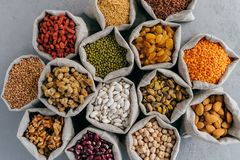 Dried food, harvest and protein from plant concept. Set of small hessian sacks filled with legumes, buckwheat, walnuts, banyan,. Chickpeas, muleberry and other stock photography