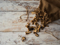 Dried forest Mushrooms in a old bag on wooden table, top view. Text space Royalty Free Stock Images