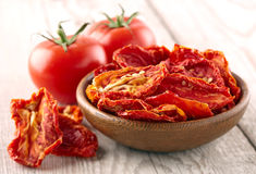 Dried and fresh tomato. On a wooden background Royalty Free Stock Images
