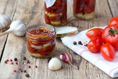 Dried and fresh tomatoes on old wooden table. Dried and fresh tomatoes with garlic and rosemarin on white napkin on old wooden table Stock Photo