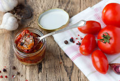 Dried and fresh tomatoes on old wooden table. Dried and fresh tomatoes with garlic and rosemarin on white napkin on old wooden table Stock Photos
