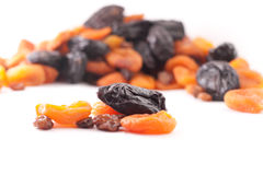 Dried fruit. Some dried fruit on the background of a large number of dried fruits isolated on a white background royalty free stock photo