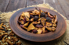 Dried fruit apples, pears, apricots, berries and nuts in a bowl on dark wooden background. Royalty Free Stock Photo