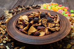 Dried fruit apples, pears, apricots, berries, raisins and nuts in a bowl on dark wooden background. Royalty Free Stock Photo