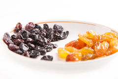 Dried fruit black and withe raisins on plate Royalty Free Stock Photo