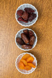 Dried fruit in bowls. Three kinds of dried fruit in bowls including figs, apricots and prunes Stock Photo