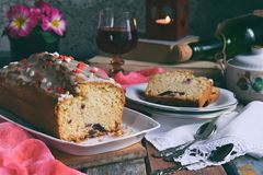 Dried fruit cake with raisins, apricots, cherry and glass of red wine, bottle and flower rustic wooden background. Valentines day. Still life. Sliced freshly royalty free stock photo