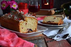 Dried fruit cake with raisins, apricots, cherry and glass of red wine, bottle and flower rustic wooden background. Valentines day. Still life. Sliced freshly royalty free stock images