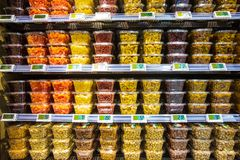 Dried fruit containers on shelves inside a supermarket. Multicolors. ROME, ITALY. December 05, 2018: Numerous containers of dried fruit placed on shelves inside royalty free stock images