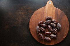 Dried dates on a wooden brown background stock image