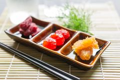 Dried fruit. Dried strawberries, dried tomatoes, pineapple preserves in a small ceramic bowl with chopsticks and Ice water on bamboo place mat. Close up Stock Photography