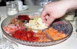 Dried Fruit. Hand takes the plate with dried fruit Royalty Free Stock Photography