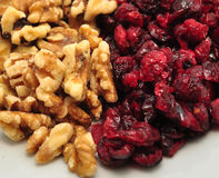 Dried Fruit and Nut Snack. Whole and organic Dried Cranberries with lightly salted walnuts in a close up shot stock photo