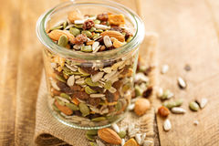 Dried fruit and nuts trail mix. With almonds, raisins, seeds and apples in a glass jar Stock Images