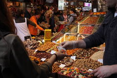 Dried fruit stand and customer at the market La Boqueria, Barcelona. Stock Image