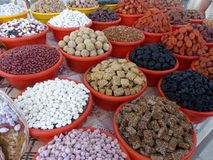 Dried fruit and sweets exposed in colored bowls in a market of Uzbekistan. A lot of bowls exposed. Red and yellow colored bowls. Bowls in a market. Market of Stock Photography