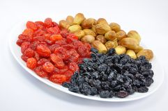 Dried Fruit on White Plate. Dried Dates, Cornelian Cherries and Black Raisins on White Plate Isolated Royalty Free Stock Photos