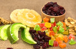 Dried fruits from candied fruits, cranberries, pomelo, pineapple. Walnuts scattered on sackcloth tablecloths Royalty Free Stock Photos