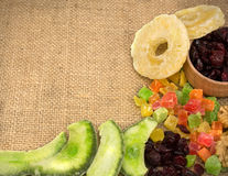 Dried fruits from candied fruits, cranberries, pomelo, pineapple. Walnuts scattered on sackcloth tablecloths Stock Photo