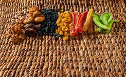 Dried fruits, nuts and candied fruits spread over a wicker surface royalty free stock photo