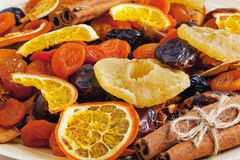 Dried fruits and cinnamon on a wooden plate Stock Photography