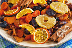 Dried fruits and cinnamon on a wooden plate on a napkin Royalty Free Stock Photo
