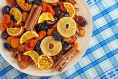 Dried fruits and cinnamon on a wooden plate on a napkin Royalty Free Stock Photos