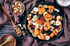 Tasty dried Fruits and Nut Mix bowl. Dried Fruits and Nut Mix bowl - banana slices, apricots, raisins, prunes, cherries and cashew on a rustic table with honey royalty free stock photography