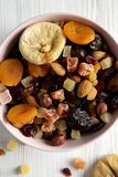 Dried fruits and nut mix in a pink bowl over white wooden surface top view. Overhead, from above, flat lay. Close-up.  royalty free stock photos