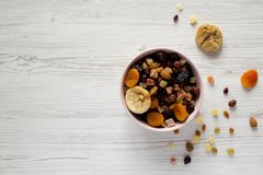 Dried fruits and nut mix in a pink bowl on white wooden background, top view. Overhead, from above, overhead. Copy space.  royalty free stock photos