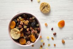 Dried fruits and nut mix in a pink bowl on white wooden background, top view. Overhead, from above, overhead.  royalty free stock image