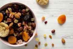 Dried fruits and nut mix in a pink bowl on a white wooden table, top view. Overhead, from above, flat lay. Close-up.  royalty free stock images