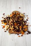 Dried fruits and nut mix on rustic wooden board over white wooden surface, low angle view.  royalty free stock image