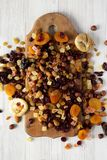 Dried fruits and nut mix on rustic wooden board over white wooden surface, top view. Overhead, from above. Close-up.  stock photos