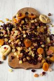 Dried fruits and nut mix on rustic wooden board over white wooden surface, side view. Close-up.  stock photography