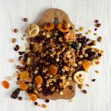 Dried fruits and nut mix on a rustic wooden board on a white wooden surface, top view. Closeup.  royalty free stock photo