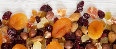 Dried fruits and nut mix on white wooden background, top view. Overhead, from above, flat lay.  stock photography