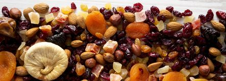 Dried fruits and nut mix on a white wooden surface, top view. Overhead, from above, flat lay.  stock photography