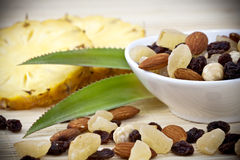 Dried fruits and nuts. A display of a cup of a variety of tropical dried fruits including nuts and raisins on a bamboo mat background with fresh slices of stock photos
