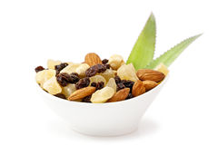 Dried fruits and nuts. Cup of a variety of tropical dried fruits including nuts and raisins on white background with fresh leaves of pineapple Stock Image
