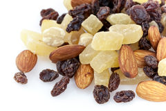 Dried fruits and nuts. Variety of tropical dried fruits including nuts and raisins on white background on a corner Royalty Free Stock Image