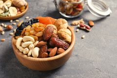 Dried fruits and nuts in dishware on table. Space for text stock photography