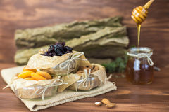 Dried fruits and nuts organic healthy mix with honey on rustic background. Stock Images