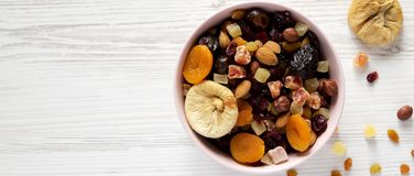 Dried fruits and nuts in a pink bowl over white wooden background, top view. Overhead, from above, flat lay. Copy space royalty free stock image
