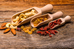Dried fruits and nuts in spoons on natural wood Stock Image