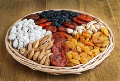 Dried fruits and nuts. In a wicker dish on wood stock photography