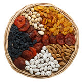 Dried fruits and nuts in a wicker plate. Isolated on white Royalty Free Stock Photography