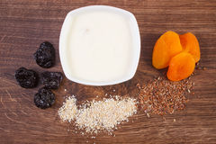 Dried fruits, oat bran, linseed and yoghurt in bowl, increase metabolism Stock Photo
