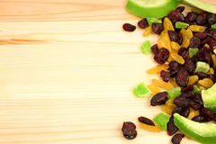 Dried fruits from pomelo, cranberries, candied fruits, raisins s. Cattered on a wooden board on the right Stock Photos