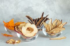 Dried fruits slices of peach, apple, pumpkin, banana in glass bowls. Dried fruits slices peach, apple, pumpkin, banana in glass bowls on light grey concrete stock image